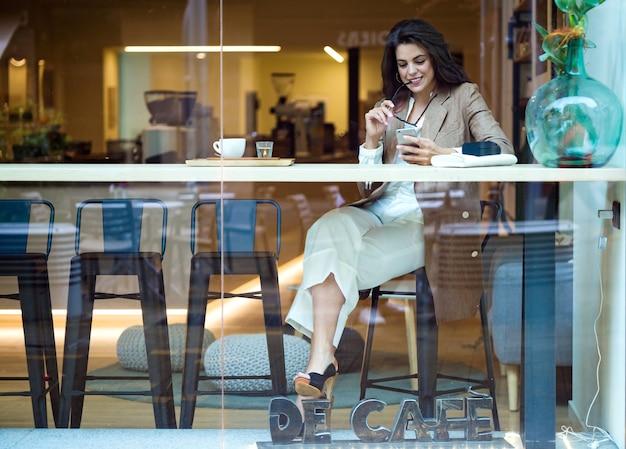 Foto de uma atraente jovem empresária enviando mensagens de texto com seu telefone celular no café.