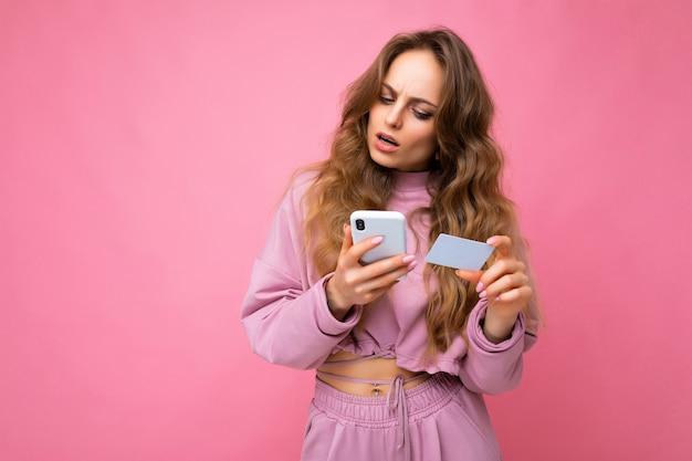 Foto de uma atraente jovem loira encaracolada, perguntando de forma atraente, vestindo roupas rosa isoladas sobre rosa