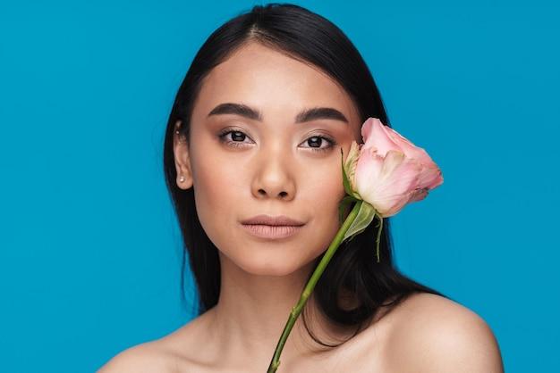 Foto de uma bela jovem asiática posando isolada na parede azul com flor.