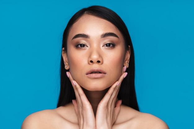 Foto de uma bela jovem asiática séria posando isolada na parede azul.