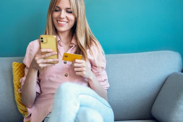 Foto de uma bela jovem compras online com cartão de crédito e smartphone enquanto está sentado no sofá em casa.
