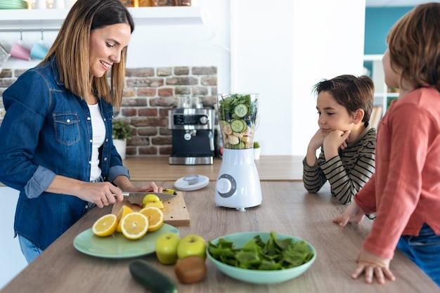 Foto de uma bela jovem cortando uma maçã para preparar bebida desintoxicante enquanto seus filhos a procuram na cozinha.