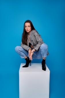 Foto de uma bela jovem em um top preto e calça jeans senta-se em cubos em uma parede azul