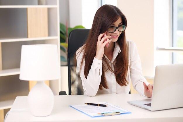 Foto de uma bela jovem empresária cuidando da papelada enquanto está sentado em uma mesa no escritório.