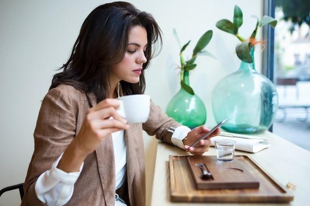Foto de uma bela jovem empresária enviando mensagens de texto com seu telefone celular no café.