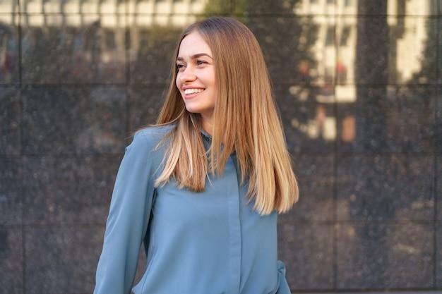 Foto de uma bela jovem empresária vestindo uma camisa de chiffon azul em pé e posando na parede de mármore cinza