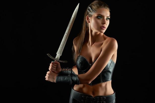 Foto de uma bela jovem guerreira amazona posando em posição de combate com uma espada na parede negra proteção da feminilidade segurança guardião guarda confiança arma lutadora.