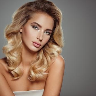 Foto de uma bela jovem loira com cabelo encaracolado. closeup rosto atraente e sensual de mulher branca. maquilhagem de olhos esfumados.