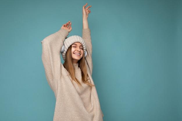 Foto de uma bela jovem loira e sorridente, vestindo um suéter bege de inverno e um chapéu isolado
