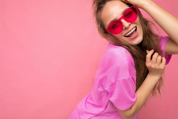 Foto de uma bela jovem loira escura, sorridente, feliz, vestindo roupas casuais e elegantes