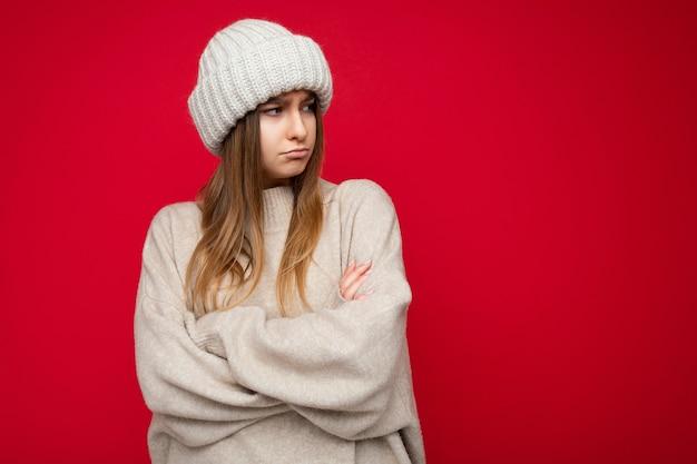 Foto de uma bela jovem loira morena ofendida, ressentida, isolada sobre uma parede de fundo vermelho, vestindo uma blusa quente e um chapéu de inverno olhando para o lado com as mãos cruzadas