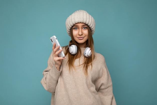 Foto de uma bela jovem loira morena sexy vestindo um suéter bege elegante e uma malha bege