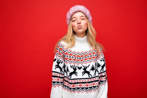 Foto de uma bela jovem loira muito positiva, fofa, isolada sobre uma parede de fundo vermelho, vestindo um suéter de inverno e um chapéu rosa dando um beijo
