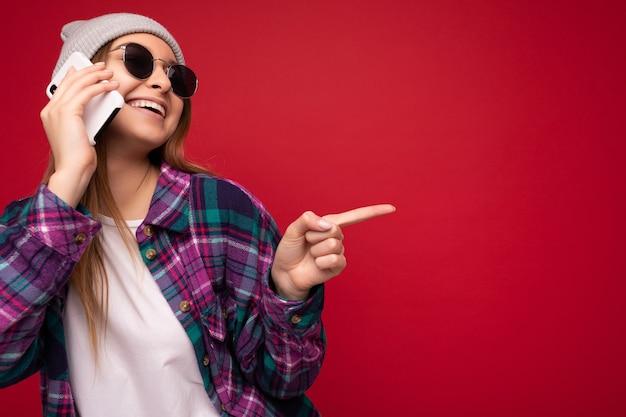 Foto de uma bela jovem loira positiva e feliz vestindo uma camisa roxa hipster e camiseta branca casual