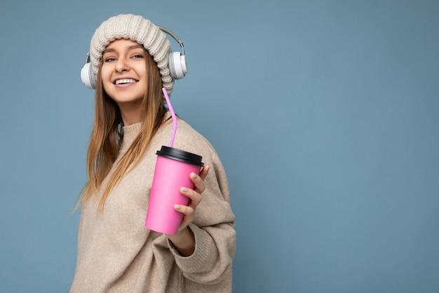 Foto de uma bela jovem loira sorridente e alegre, vestindo um suéter bege de inverno e um chapéu