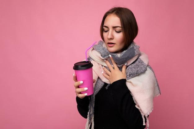 Foto de uma bela jovem morena triste vestindo um suéter preto e um lenço quente isolado sobre um fundo rosa segurando uma xícara de café de papel para maquete, bebendo uma bebida quente e rindo