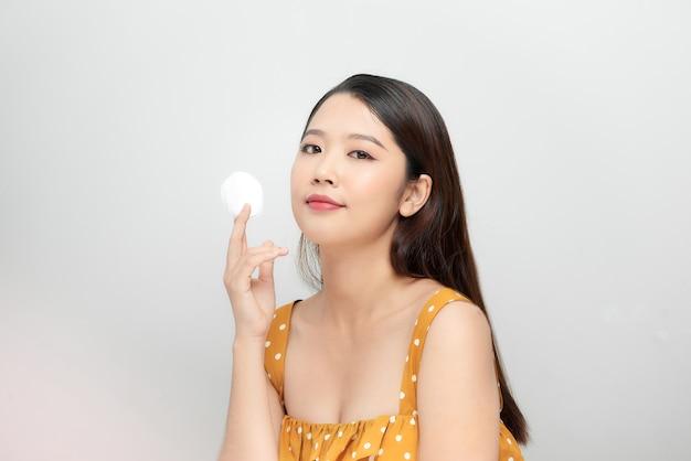 Foto de uma bela jovem muito asiática com pele saudável posando nua isolada sobre o fundo da parede branca, segurando almofadas de algodão.