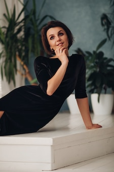 Foto de uma bela jovem mulher branca com cabelo longo loiro, rosto bonito, maquiagem brilhante, brincos brilhantes em um vestido preto longo