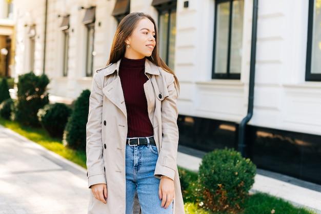 Foto de uma bela jovem olhando e sorrindo perto de um café em uma cidade