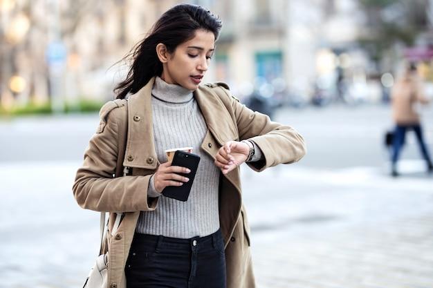 Foto de uma bela jovem olhando o relógio enquanto espera um amigo na rua.