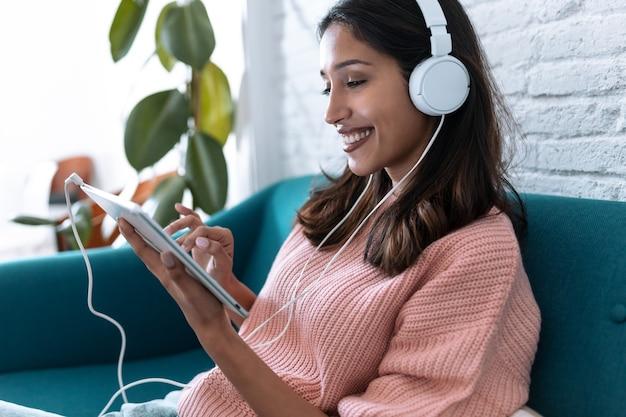 Foto de uma bela jovem ouvindo música com o tablet digital enquanto está sentado no sofá em casa.