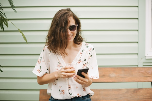 Foto de uma bela jovem segurando um copo usando o celular fora