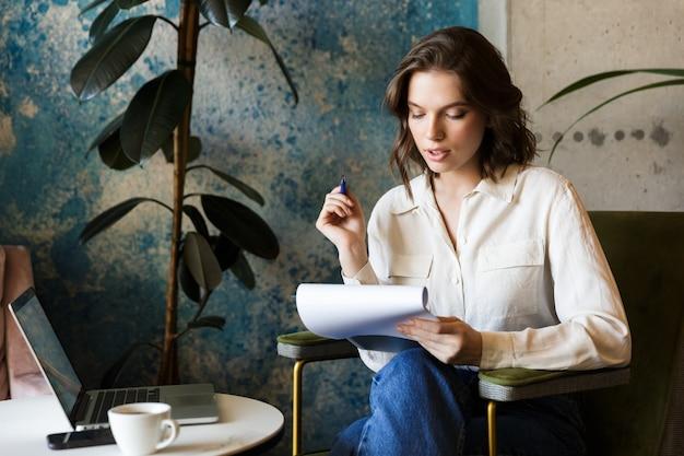 Foto de uma bela jovem sentada no café dentro de casa, trabalhando com o laptop segurando documentos.