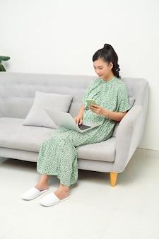 Foto de uma bela jovem usando seu telefone celular enquanto trabalhava com o laptop sentado no sofá em casa.