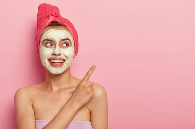Foto de uma bela modelo feminina relaxada aponta o dedo indicador para o espaço da cópia, aplica máscara de argila natural na pele problemática e reduz a secura