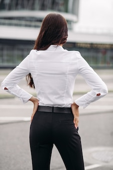 Foto de uma bela mulher caucasiana com longos cabelos escuros ondulados em uma camisa branca, calça preta e salto alto parece um prédio alto