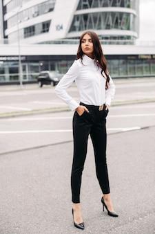 Foto de uma bela mulher caucasiana com longos cabelos escuros ondulados em uma camisa branca, calça preta e salto alto posando para a câmera
