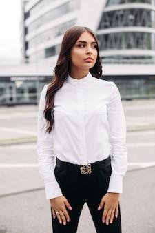 Foto de uma bela mulher caucasiana com longos cabelos escuros ondulados em uma camisa branca, calça preta e salto alto, posando para a câmera