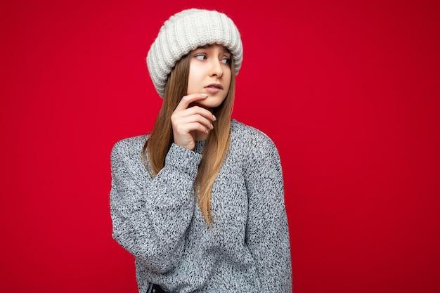 Foto de uma bela mulher loira pensativa triste e preocupada em pé isolado sobre a parede de fundo vermelho, vestindo uma blusa cinza e um chapéu bege, olhando para o lado. espaço vazio, copie o espaço
