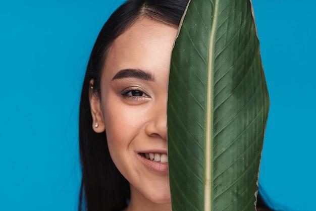 Foto de uma bela positiva sorridente jovem asiática posando isolada na parede azul com metade da face da folha da planta verde.