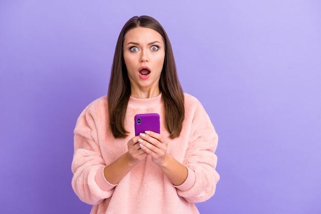 Foto de uma blogueira maluca segurando um telefone com a boca aberta na parede roxa