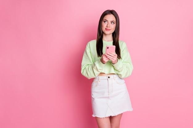 Foto de uma blogueira pensativa usando smartphone look copyspace decidir que mensagem de texto digitando mídia social conta usar roupas jeans brancas verdes isoladas sobre fundo de cor pastel