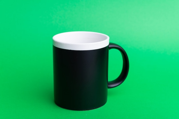 Foto de uma caneca preta no verde isolada