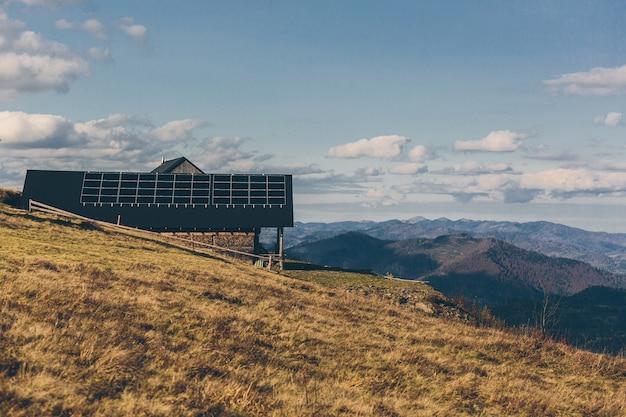 Foto de uma casa na montanha, no telhado de um painel solar, pôr do sol