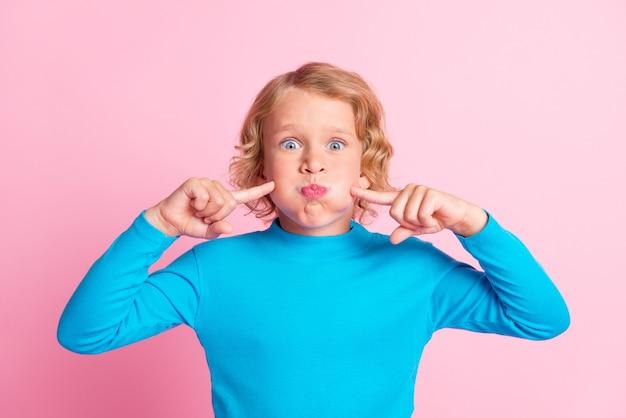 Foto de uma criança com bochechas infladas indicando dedos olhando a câmera usar gola azul com fundo de cor rosa pastel isolado