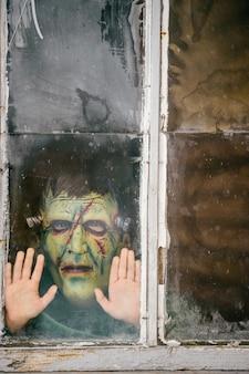 Foto de uma criança com uma máscara de monstro terrível espiando por uma janela velha e suja no inverno