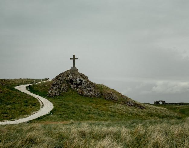Foto de uma cruz colocada em um pedestal colocado em uma colina rochosa