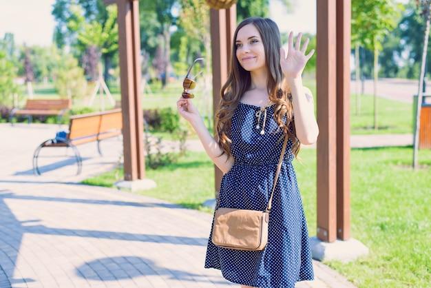 Foto de uma doce senhora satisfeita enviando uma saudação dizendo tchau para a namorada, vestindo roupas vintage retrô pontilhadas azuis segurando óculos e óculos em pé perto do gramado verde