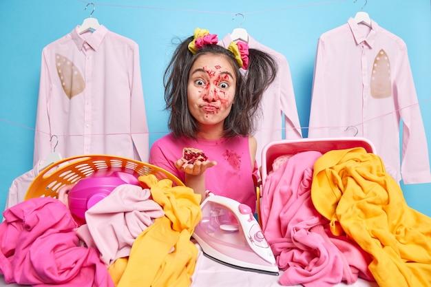 Foto de uma dona de casa asiática morena engraçada segurando um pedaço de torta com a cara suja