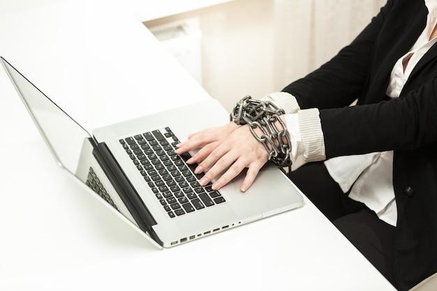 Foto de uma empresária acorrentada digitando no teclado
