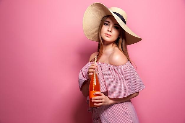 Foto de uma encantadora mulher usando chapéu de palha bebendo suco de uma garrafa de vidro isolada sobre uma parede rosa