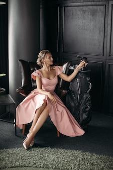 Foto de uma encantadora senhora caucasiana sentada na poltrona de couro preto e posa para a câmera