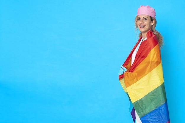 Foto de uma enfermeira sorridente com uma bandeira lgbt em um fundo azul