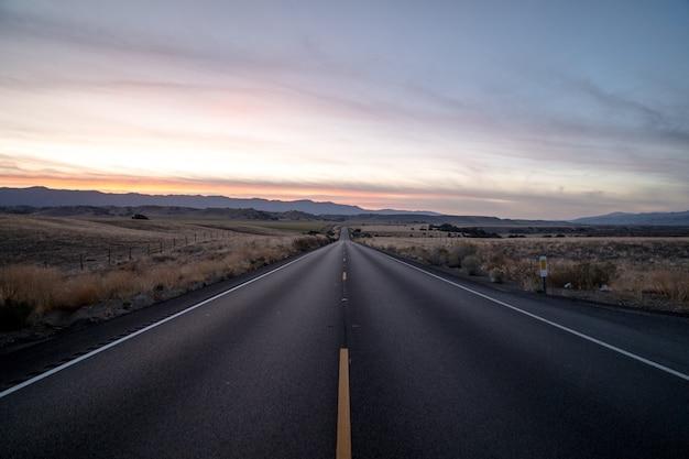 Foto de uma estrada rodeada por campos de grama seca sob um céu durante o pôr do sol