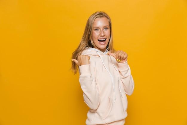 Foto de uma estudante adolescente com aparelho dentário apontando o dedo para trás em copyspace, isolada sobre fundo amarelo