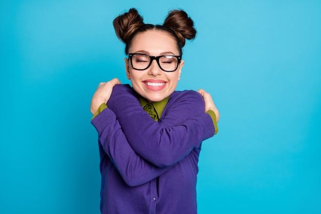 Foto de uma estudante muito feliz com dois pãezinhos de olhos fechados, abraçando a si mesma como motivação antes do exame exame especificações de desgaste camisa gola suéter violeta isolado fundo de cor azul